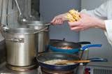 noodles and sauce preparation, interior of restaurant kitchen poster