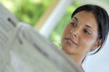 Jeune femme lisant un journal