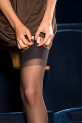 The woman clasps stockings on a leg