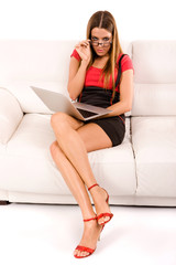 Beautiful young woman using laptop on couch