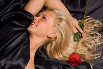 Beautiful blond girl laying on black satin.