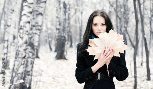 Brunette woman with maple leaves.