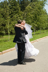 groom turning his bride on the road
