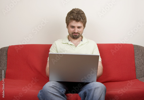 Casual man sitting on the sofa and works on the laptop