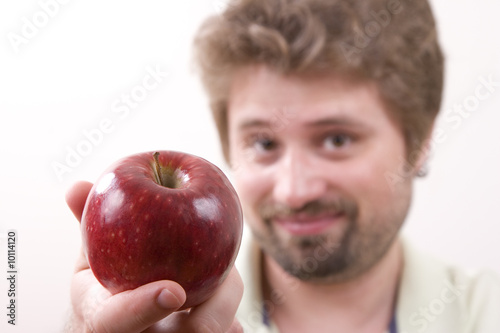 Young man is offering an apple
