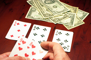 hand of the person with card for poker and rate in dollars