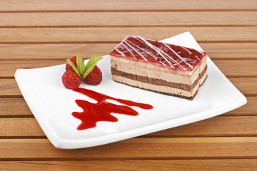 Strawberry cake with soft shadow on white dish. Shallow DOF