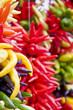 Many types of yellow and red peppers hanging in a market