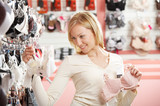 The blonde chooses a brassiere in shop poster