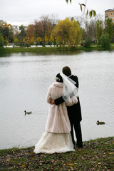 groom and bride near lake in autumn