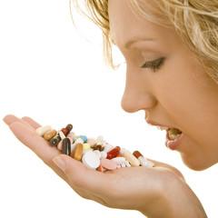 Blonde Frau hält viele bunte Tabletten vor ihrem Mund