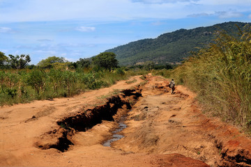 a man walking on a road to nowhere in Africa