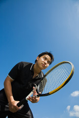 A young sporty asian tennis player receiving serve