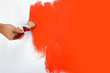 Painting the wall red with a paint brush