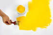 Painting the wall yellow with a paint brush