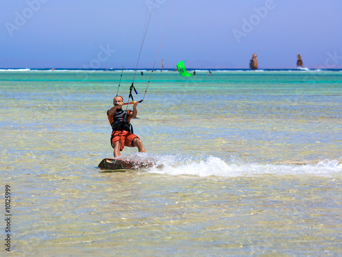 Portrait young man with kiteboard on water