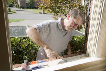 Carpenter making repairs on window frame