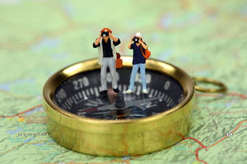 Miniature tourists taking pictures while standing on a compass