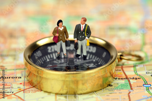 Miniature business travelers standing on a compass on a map