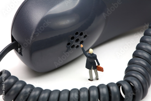 Miniature businessman in front of a phone waving for help.