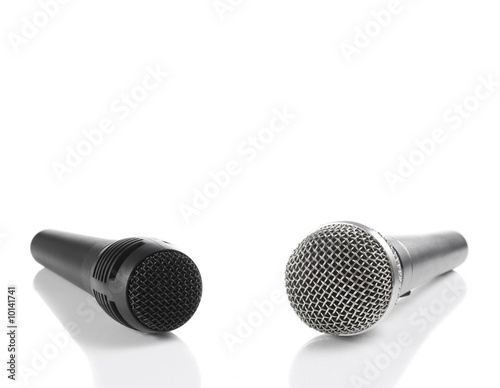 A black and a silver microphones isolated with copyspace.