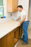 Contractor remodeling kitchen, installing cabinets poster
