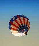 Hot air balloon passing overhead at dawn poster