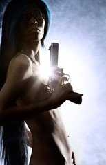 Naked beauty holding gun with smoke in background
