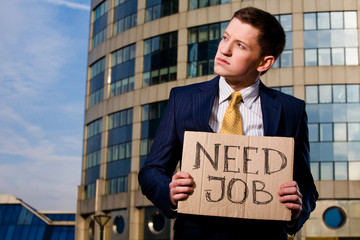 Crisis. Young businessman holding sign Need Job