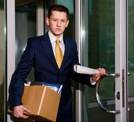 Unemployed young manager leaving business center