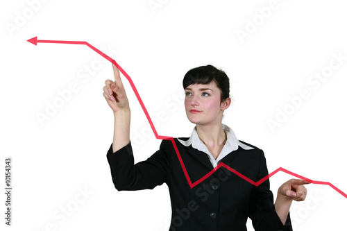 Business woman pointing at a red graph