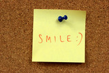 Yellow small sticky note on an office bulletin board. Smile! poster