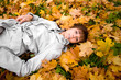 Young woman laying on a autumn leaves. Focus on the face.