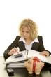 Blonde Frau am Schreibtisch benutzt einen Taschenrechner