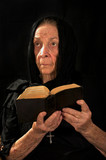 Old Catholic nun in prayer holding bible and rosary poster