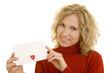 Blonde Frau zeigt einen Briefumschlag mit Herz