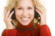 Lachende blonde Frau hört Musik mit Kopfhörern