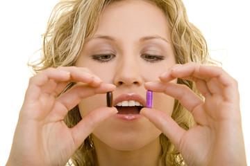 Blonde Frau hält zwei Pillen vor dem offenen Mund