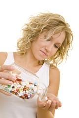 Blonde Frau schüttet viele bunte Tabletten in ihre Hand