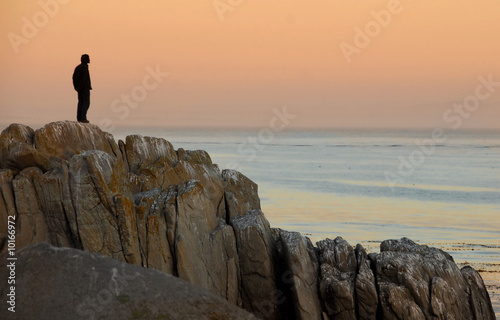 Man by himself on cliff overlooking sea