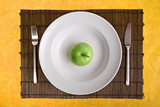 white dish and green apple on bamboo board poster