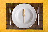 white dish with grain on bamboo board with yellow background poster