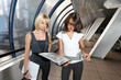 Two businesswomen looking into folder in futuristic interior