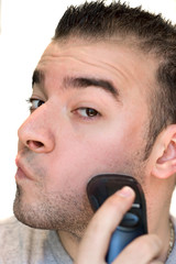 A closeup of a young man shaving his beard off.