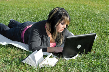 A young student using her laptop computer on a nice day.