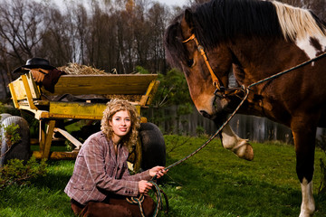 Lovely blond woman sitting by horse outdoors