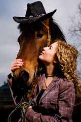 Lovely blond woman standing by horse outdoors