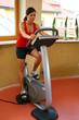 Frau im Fitness Studio auf einem Hometrainer