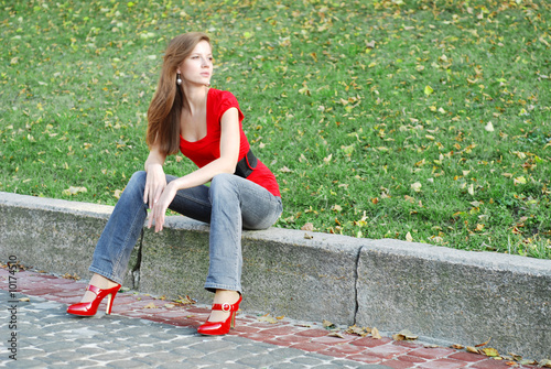 beautiful woman sit on a road kerb in park