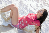 The beautiful young woman lies in waves on sea coast